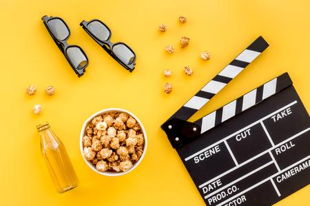 영화 감상을위한 간식. 팝콘 및 clapperboard, 노란색 배경 상위 뷰 안경 가까운 음료수. 스톡 콘텐츠