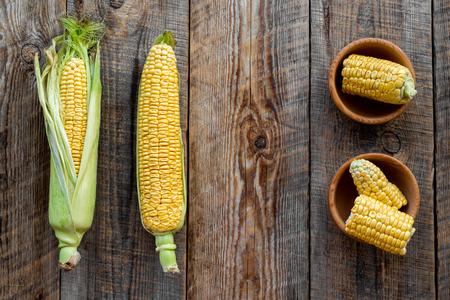 cutted: Organic farm food. Cutted corn cobs on rustic wooden background top view.