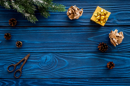 New years background. Christmas present, spruce branches, pine cones on blue wooden background top view.