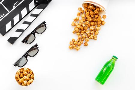 Nourriture pour regarder le film. Popcorn et soda près de clapperboard, verres sur fond blanc vue de dessus Banque d'images - 84551618