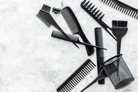 styling hair with combs and hairdresser tools in barbershop on gray stone background top view mock-up