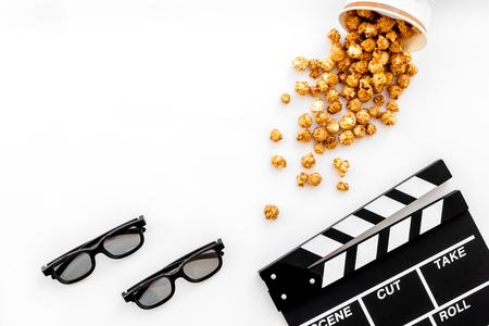 Aller au cinéma. Clapetboard, lunettes et popcorn sur fond blanc vue de dessus. Banque d'images - 84557523