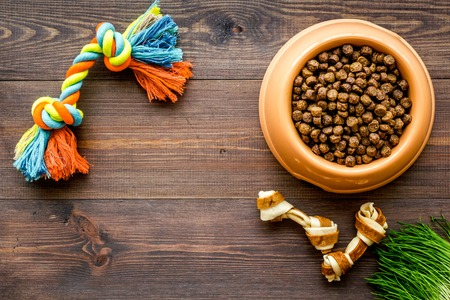 large bowl of pet - dog food with toys on wooden background top view mockup Stock Photo