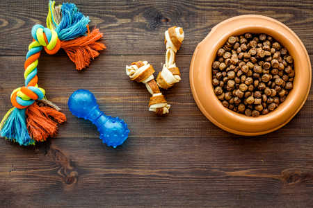 Orange plastic bowl full and overflowing with dry pet - dog food bits and toys on wooden table background top view Stok Fotoğraf
