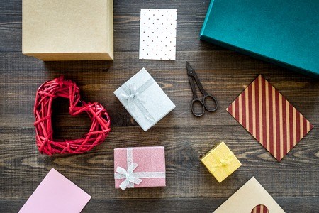 Preparing gift and greeting card. Gift boxes, card, envelope, ribbon dark wooden background top view. Stock Photo