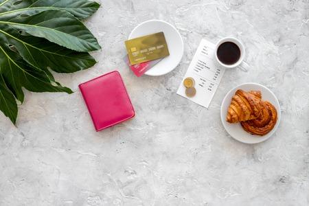 総: Paying at cafe by card. Bill and coins near coffee, croissant and wallet on light stone table top view.