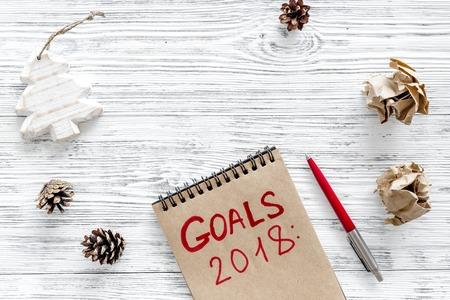 新年の目標を設定します。灰色の木製の背景平面図上にペンに近いノート。
