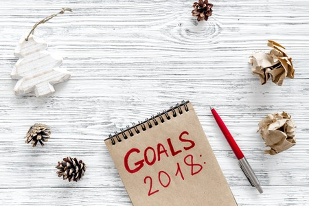 Set a goal for new year. Notebook near pen on grey wooden background top view.