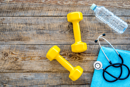 Sport and health. Fitness. Dumbbells and stethoscope on wooden background top view. Reklamní fotografie - 84712498