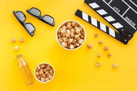 Snacks voor film kijken. Popcorn en frisdrank dichtbij clapperboard, glazen op gele hoogste mening als achtergrond.