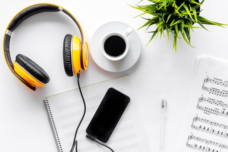 Desk of musician for songwriter work set with headphones and smartphone on white background top view mockup