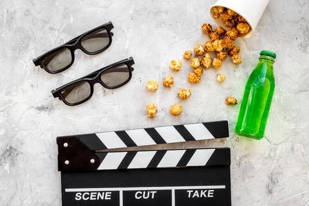 Nourriture pour regarder le film. Popcorn et soda près de clapperboard, verres sur fond gris copyspace vue de dessus Banque d'images - 84804496