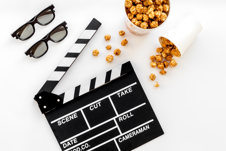 To go to the cinema. Clapperboard, glasses and popcorn on white background top view