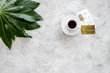 Betaal restaurantrekening. Rekening, bankkaart, muntstukken dichtbij kop van koffie op de lichte mening van de lijstbovenkant.
