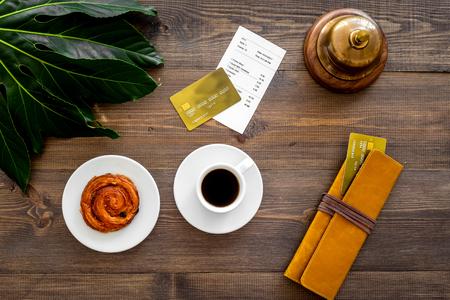 総: Paying at cafe by card. Bill near coffee, bun and wallet on dark wooden table top view.