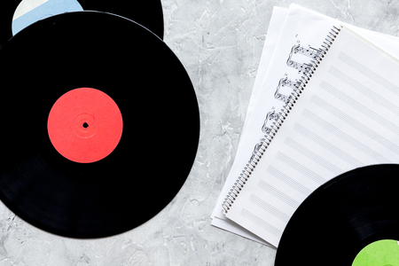 records with paper note in music studio for dj or musician work on stone desk background top view mock-up