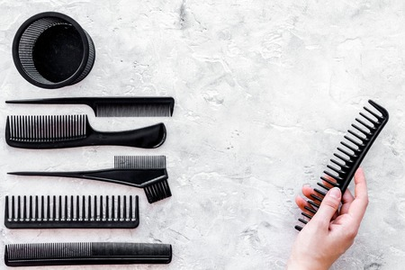 black combs, brushes for hairdresser work set on stone desk background top view mock up Stock Photo