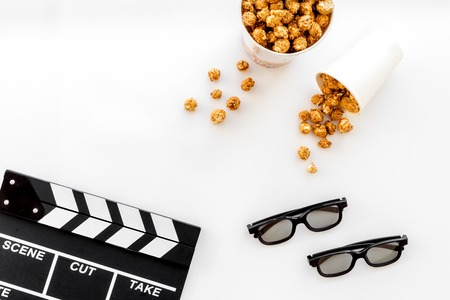 filmmaker: To go to the cinema. Clapperboard, glasses and popcorn on white background top view.
