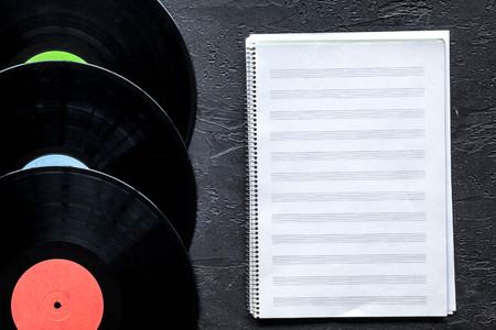 songwriter or dj work place with notebook and vynil record on black desk background top view mockup