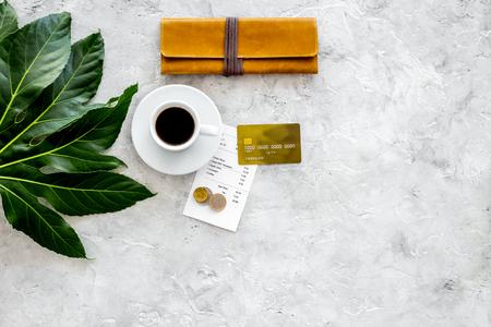 Hoe veel. Restaurantrekening, bankkaart, portefeuille, muntstukken dichtbij kop van koffie op de lichte mening van de steenlijstbovenkant copyspace