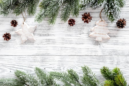 Christmas background. Toys, spruce branches, pine cones on light wooden background top view.