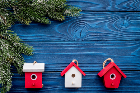 house toys to decorate christmas tree for new year celebration with fur tree branches on blue wooden table background top veiw mockup
