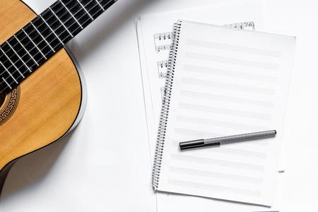 Trabajo de músico con papel en blanco para notas y fondo de tabla blanca de guitarra espacio de vista superior para texto Foto de archivo - 85134223
