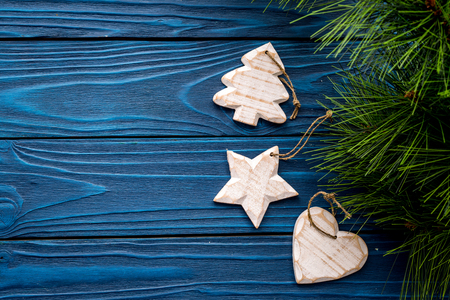 Christmas eve set with spruce branches and tree, heart and star toys on blue wooden background top veiw mock-up