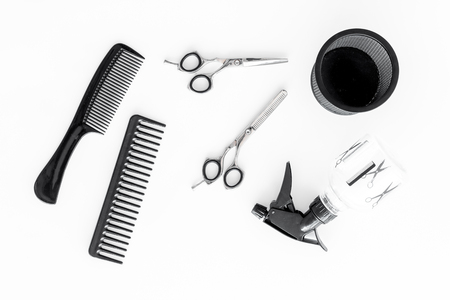 hairdresser working desk with tools for hair styling on white desk background top view