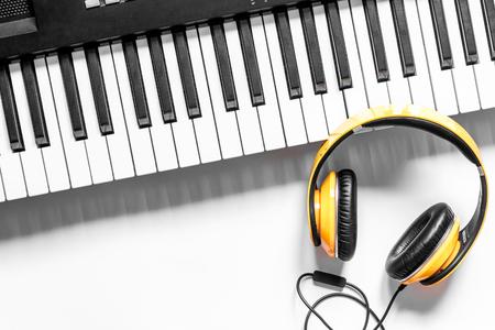 ミュージシャン作業テキストの白いテーブル背景トップ ビュー空間にシンセサイザーとヘッドフォン セット