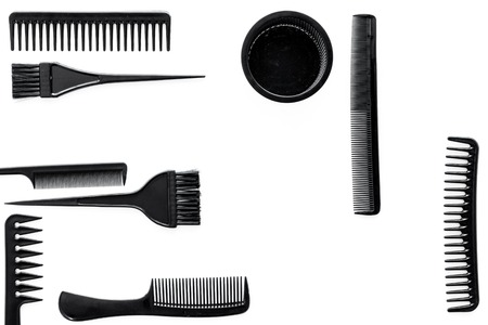 Styling hair with combs and hairdresser tools in barbershop on white background top view