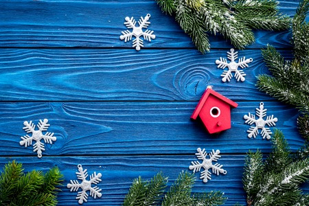 new year 2018 greeting with spruce branches and decorations with house toys on blue wooden table background top veiw space for text