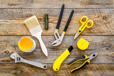 constructor desk with set of building implements and brushes wooden desk background top view
