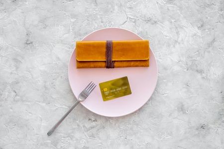 食事は終わりだ請求書を支払う。灰色の石のテーブルの上の空の版の銀行カードそして財布