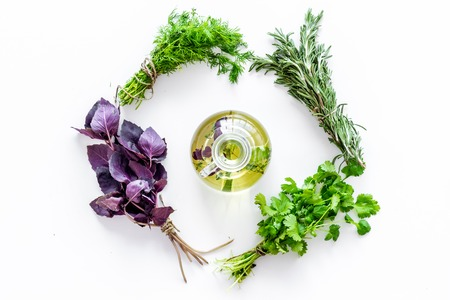 natural oil and fresh greenery for restaurant cooking on white kitchen table background top view