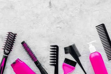 pink combs, brushes and spray for hairdresser work on stone desk background top view mockup Stock Photo