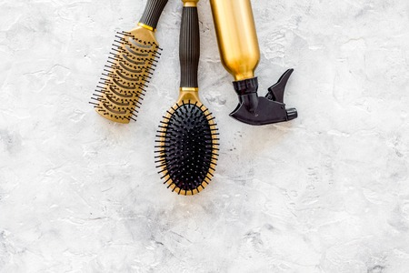 golden combs and spray for hairdresser work on stone desk background top view mock-up Stock Photo