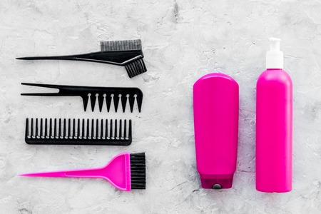 pink combs, brushes and spray for hairdresser work set on stone desk background top view