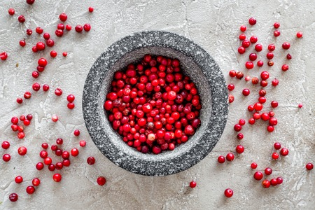 berries in mortar for making spices in food set on stone table background top view