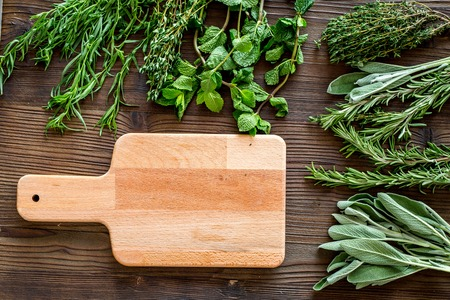 drying fresh herbs and greenery for spice home food on wooden kitchen desk background top view space for text