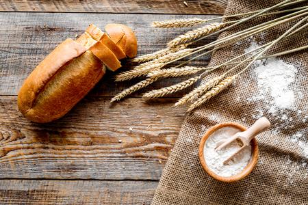 木製の机の背景トップビューにベーカリーショップで小麦粉と新鮮なおいしいパン 写真素材
