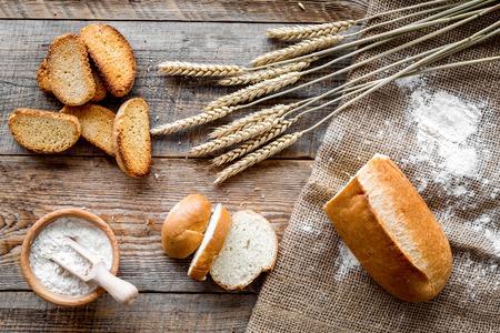 bakken verse wheatenbrood op bakkerij werktafel houten achtergrond bovenaanzicht Stockfoto