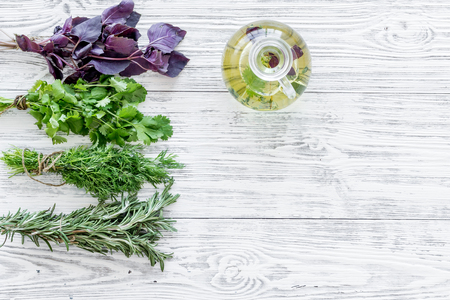 greenery with natural oil for cooking on light wooden kitchen table background top view mock-up