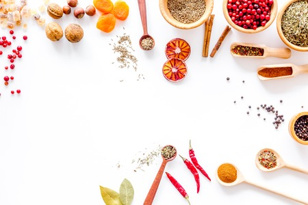 Kitchen table with spices and dry herbs on white kitchen background top view mock up
