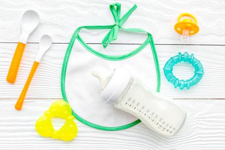 Mère soins du lait maternel dans une bouteille et la grippe du corps de la nourriture saine avec bavoir pour le bébé alimentation sur fond blanc vue de dessus Banque d'images - 85756156