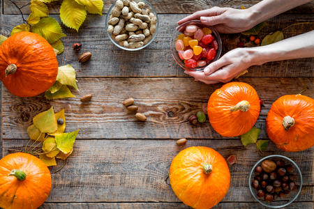 Pumpkin harvest. Pumpkins near nuts and autumn leaves on wooden background top view copyspace Stock Photo