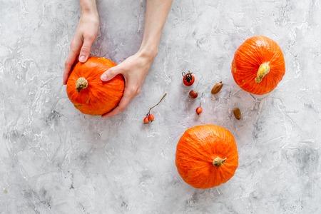 Pumpkin harvest. Pumpkins near nuts on grey background top view copyspace
