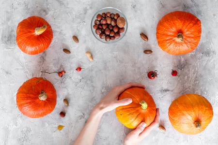 Pumpkin harvest. Pumpkins near nuts on grey background top view