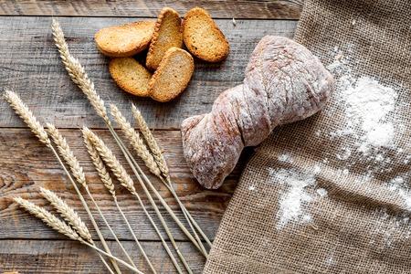 Bovenaanzicht van tarwe en brood op een houten tafel