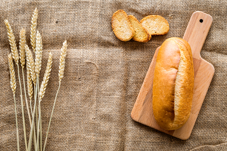 Top view of wheat and breads on a wooden table